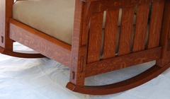 Detail side of Morris rocker showing the hand selected quartersawn white oak in the vertical slats, the steam bent rockers, double pinned true through tenon of the front seat rail and the smaller pinned tenon of the side rail.