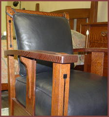 Detail of the dramatic design elements of the tapered arm which curves out in the center as it arches upward, the unusual wide single slat under the arm and the unique long corble attached to the slat under the arm.  True Ebony inlay in the front leg and back of chair. Please note the double pinned joinery where the top crest rail of the back is mortised into the top of the back leg and the large pinned through tenon extends above the top of the arm.