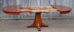 Shown open without leaves, exhibiting the thick hard maple dovetail table glides used also by Gustav Stickley.