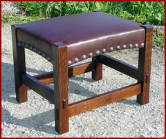 The same form with the addition of tacks.  Please see our model #100-T with tacks.  Gustav Stickley produced this footstool with and without tacks, he also produced this same form simplified without the arches and trough-tenons. We chose to offer the replica of the more desirable form, with and without tacks.