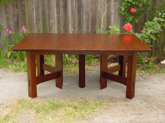 Table shown open with two leaves. Measures 6' long.  When table is opened, the large center leg separates to reveal hidden center leg which supports the leaves.