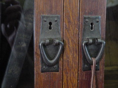 Close-up of hand-hammered iron pulls and quarter-sawn doors.