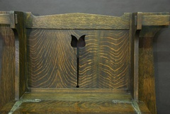 Floral cut-out on back panel of book-matched quarter-sawed oak of spectacular grain above pewter strap hardware.