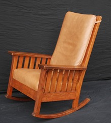 L & J G Stickley uncommon large high back rocking chair with slats under the arms, signed.